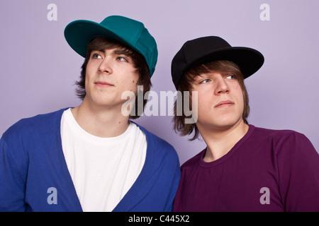 Two teenage boys wearing baseball caps looking away, studio shot - Stock Photo