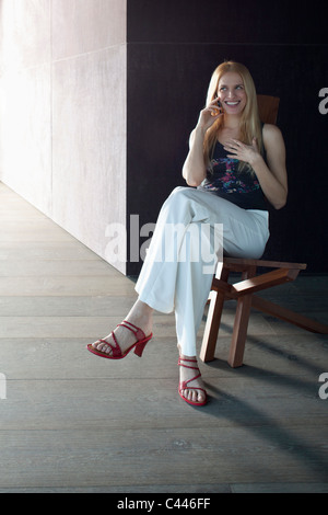 Woman sitting chatting on phone and smiling. - Stock Photo