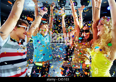 Photo of excited teenagers raising their arms under falling confetti - Stock Photo