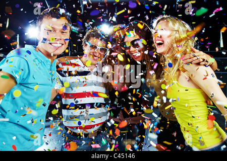 Photo of excited teenagers embracing at party under falling confetti - Stock Photo