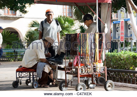 Catching Up on the Morning Gossip Over a Clean and Polish at the Shoe Shine Stall, Zocalo Town Square, Merida, Yucatan - Stock Photo