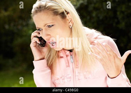 Woman shouting at her phone - Stock Photo