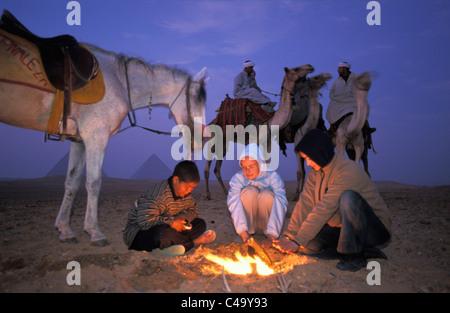 EGYPT. Giza, near Cairo. Pyramids. Camel drivers and tourists at campfire - Stockfoto