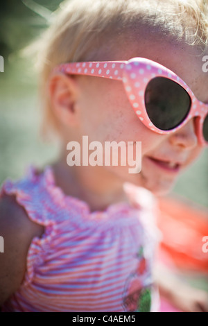 Toddler Girl wearing Sunglasses Smiling - Stock Photo