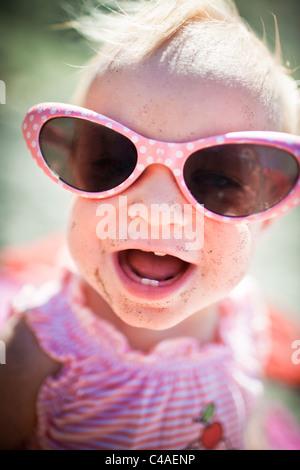 Kleinkind Mädchen mit großen Sonnenbrille am Strand - Stockfoto