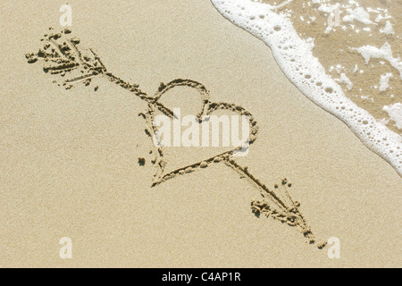 Heart pierced by Cupid's arrow drawn in the sand - Stockfoto