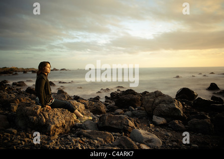 Woman, sunset, rocky shore, New Zealand. Combined long exposure. - Stock Photo