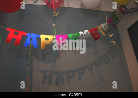 A celebration with a Happy Birthday banner sign hanging on the ceiling; perfect for a childs birthday party. - Stock Photo