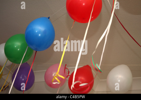 A celebration with many colourful balloons hanging on the ceiling or on the floor, perfect for a childs birthday - Stock Photo