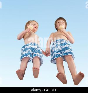 Boys in swim suits eating ice cream - Stock Photo