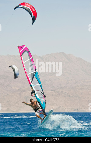 A windsurfer performing tricks on the red sea at the resort of Eilat in Israel. - Stock Photo