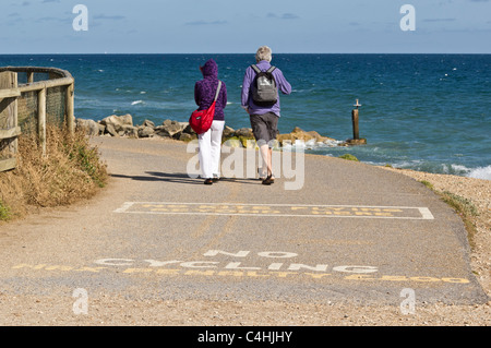 Walkers on coastal path with 'No Cycling' and 'No Kite Flying' signs painted on path in foreground - Stock Photo