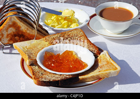 Buttered toast and marmalade with cup of tea to the rear, Western Europe. - Stock Photo