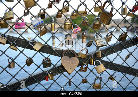 Love Locks attached to the Pont des Arts over the river Seine in Paris, France - Stock Photo