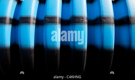 Blue and black stripes on grooved water pipe surface - Stock Photo
