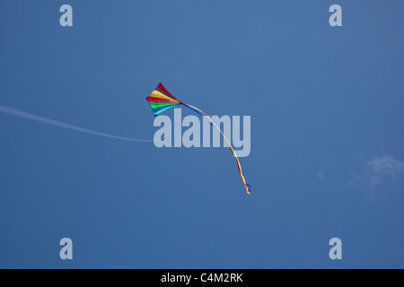 Rainbow kite flying on a string with a blue cloudy sky, Hampshire, England, U.K - Stock Photo