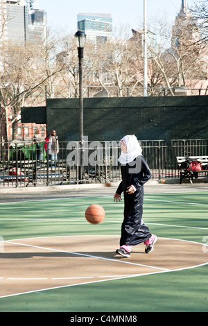 pretty young Muslim girl in head scarf with black abaya over her jeans plays with soccer ball in New York city playground - Stockfoto