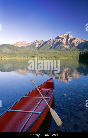 Red canoe at dawn on Pyramid Lake, Jasper National Park, Alberta, Canada. - Stock Photo