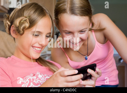 Two girls who have been playing with hair and make up look at iPhone - Stock Photo