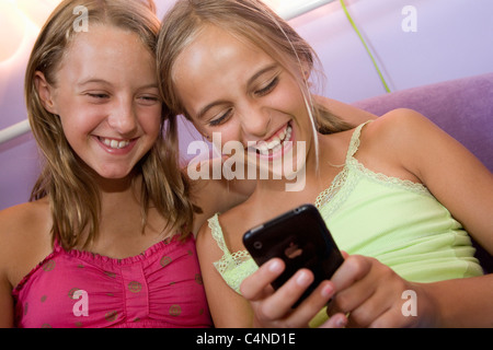 Two girls playing on iPhone - Stock Photo