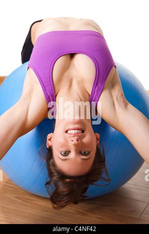 Beautiful young and athletic woman making exercises on a fitness ball - Stockfoto