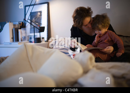 Mother holding toddler son on lap, reading bedtime story in bed - Stock Photo