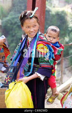 Black Hmong Ehtnic Minority Woman carrying Child in Vietnam - Stock Photo