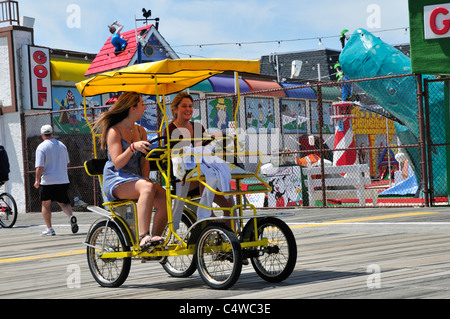 Two girls share a laugh while pedaling their surrey on the boardwalk at Ocean City, New Jersey - Stock Photo