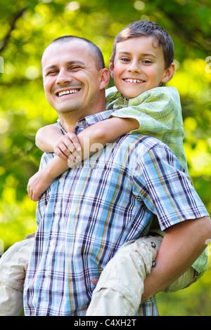 Father giving his son a piggyback ride, having fun - Stock Photo