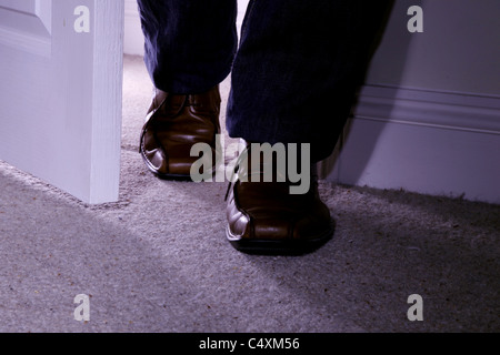 Man's feet only wearing brown shoes entering a dark carpeted room - Stock Photo