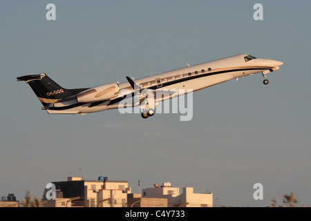 Embraer Legacy 600 business jet taking off at sunset - Stock Photo