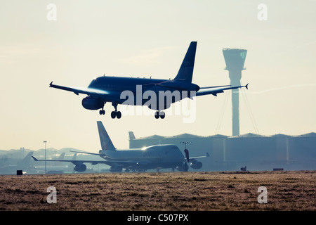 Airplane landing at London Heathrow Airport. - Stock Photo