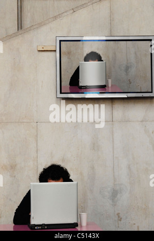 Flat screen on wall showing person in front using laptop - Stock Photo