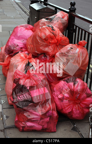 Bags of rubbish left on a pavement in Regent Street, London - Stock Photo