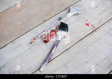 three paint brushes on the floor - Stock Photo