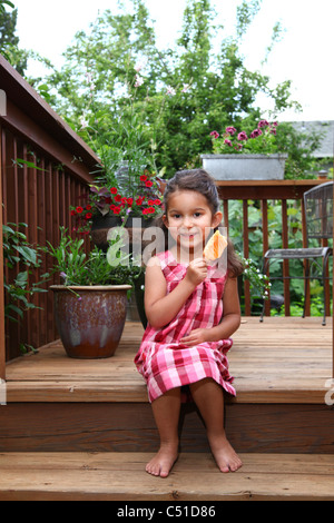 Little girl in pink plaid dress sitting on back deck eating a popsicle frozen dessert. - Stock Photo