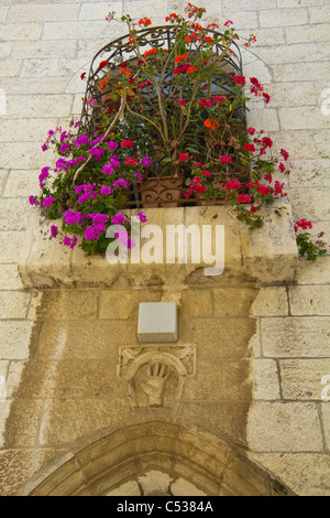 Window covered in flowers above a door with symbolic hand in the Old City of Jerusalem Israel - Stock Photo