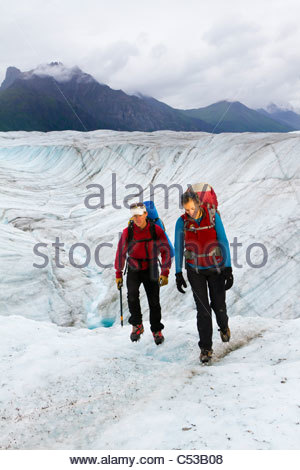 Couple hiking on Root Glacier below Donoho Peak in Wrangell-Saint Elias National Park, Southcentral Alaska, Summer - Stock Photo
