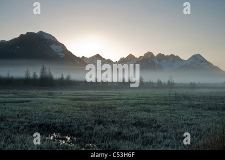 Morning fog hangs on the ground near the Copper River Highway, sunrise, Chugach Mountains, Chugach National Forest, - Stock Photo