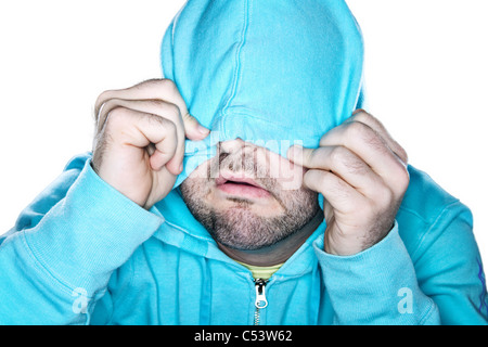 Scruffy man pulling a bright blue hoodie over his face, with a comedic expression. - Stock Photo