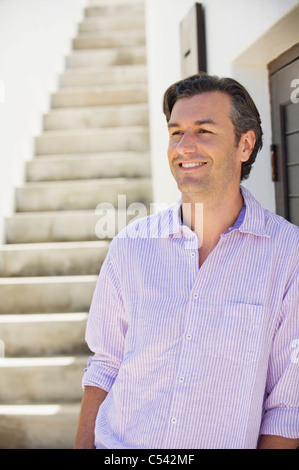 Mid adult man leaning against a wall - Stock Photo