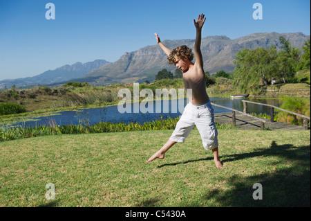 Cute little boy doing cartwheel against mountain - Stock Photo