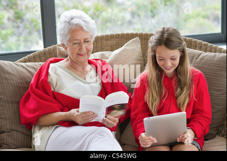 Senior woman reading a magazine with her granddaughter using a digital tablet - Stock Photo