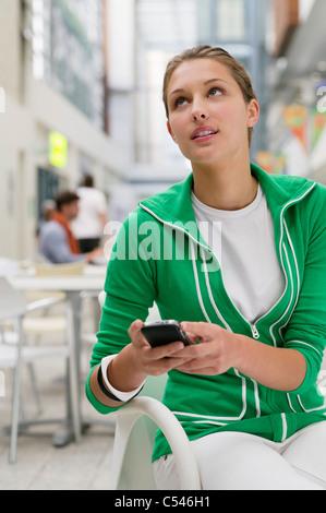 Beautiful woman using mobile phone in university lobby - Stock Photo