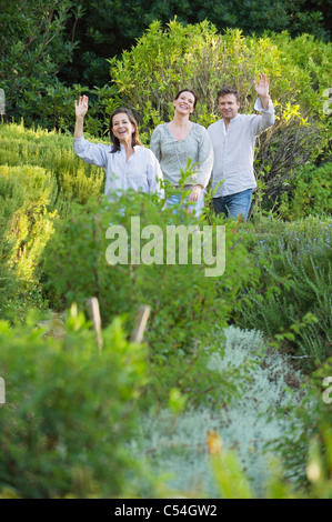 Mature couple walking with their mother and waving hand in a garden - Stock Photo