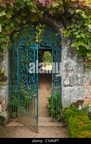 Open Wrought Iron Decorative Garden Gate Hanging Off Brick