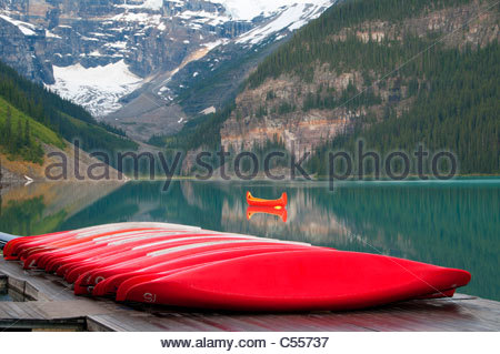 Red canoes at a lakeside, Lake Louise, Banff National Park, Alberta, Canada - Stockfoto