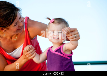 Woman helping her daughter to walk - Stockfoto