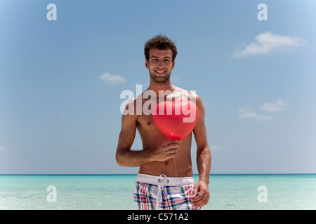 Man with heart shaped balloon on beach - Stockfoto
