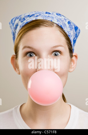 Woman blowing a bubble with gum - Stock Photo